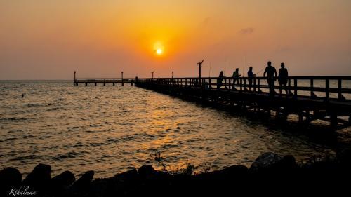 Fishing pier at sunset by Kathy Thalman